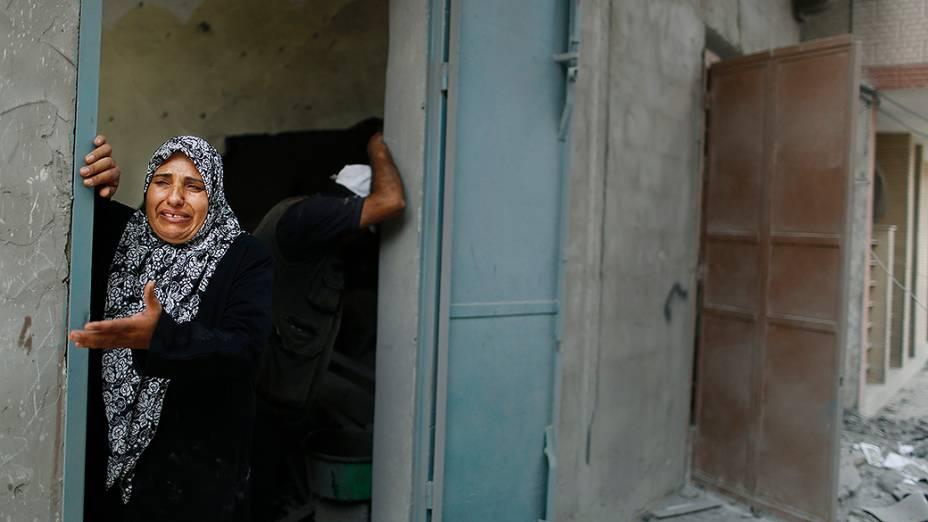 Mulher chora ao ver sua casa destruída durante ofensiva israelense no distrito de Beit Hanoun, em Gaza