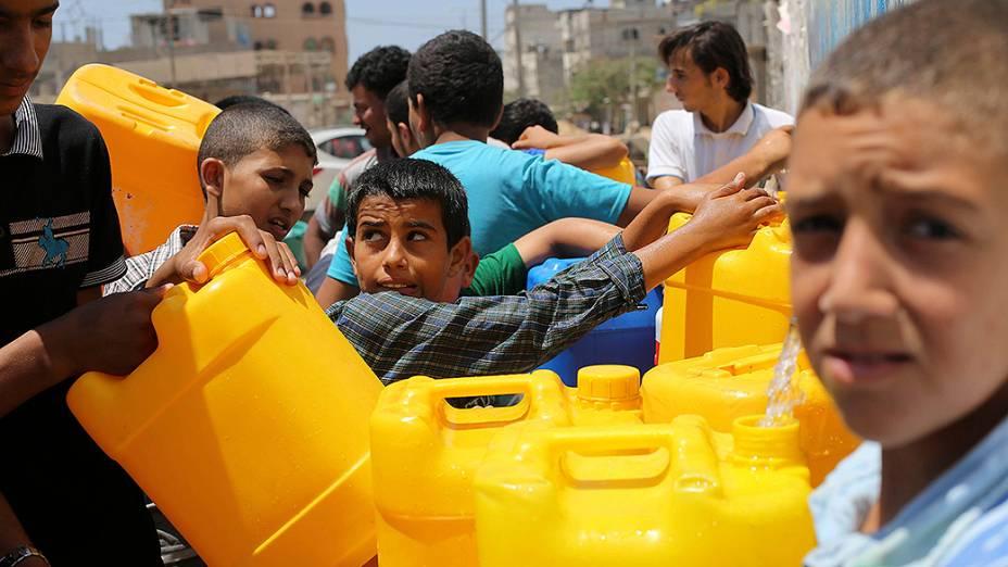 Palestinos enchem recipientes com água em torneiras públicas em Khan Younis, no sul da Faixa de Gaza