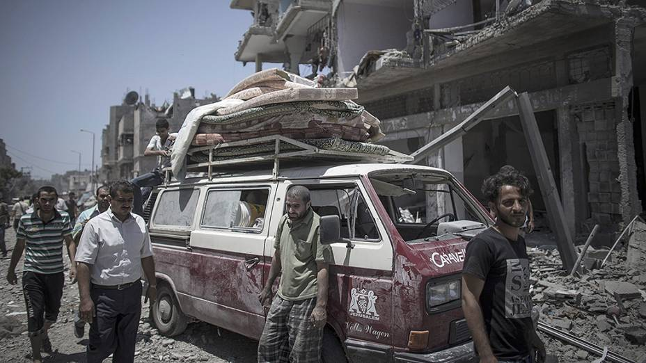 Palestinos tentam recuperar objetos em meio aos escombros no bairro Shujaiyya no leste da Cidade de Gaza