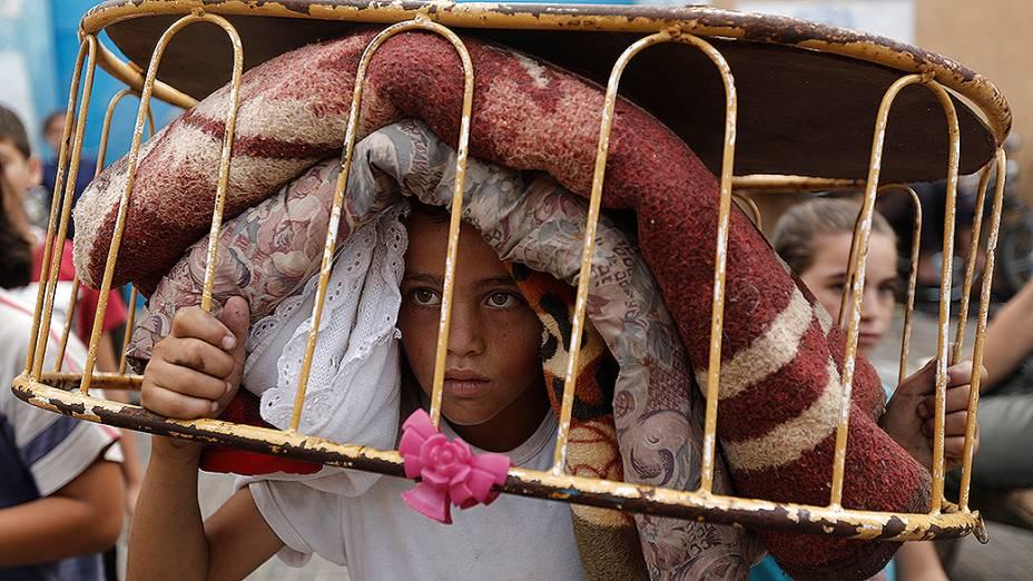 Palestino desabrigado carrega seus pertences para uma escola da ONU no norte de Gaza, durante o cessar-fogo entre Israel e o Hamas