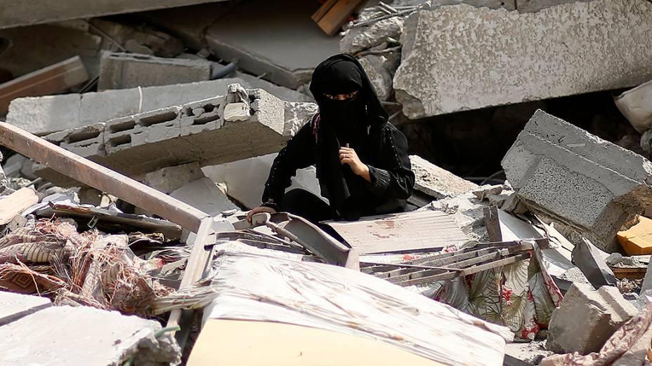 Menina palestina procura por seus pertences entre os destroços de sua casa, na Faixa de Gaza