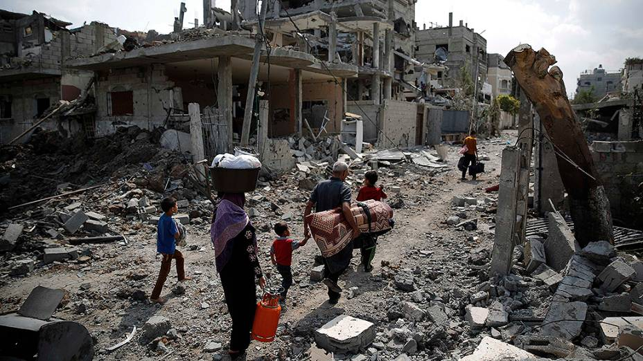 Famílias palestinas caminham entre casas destuídas por mísseis israelenses, na Faixa de Gaza
