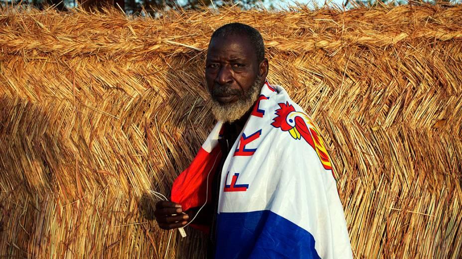 Homem com uma bandeira com o nome da França sobre os ombros durante intervenção francesa no Mali