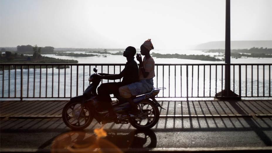 Casal anda de motocicleta no centro de Bamako, Mali