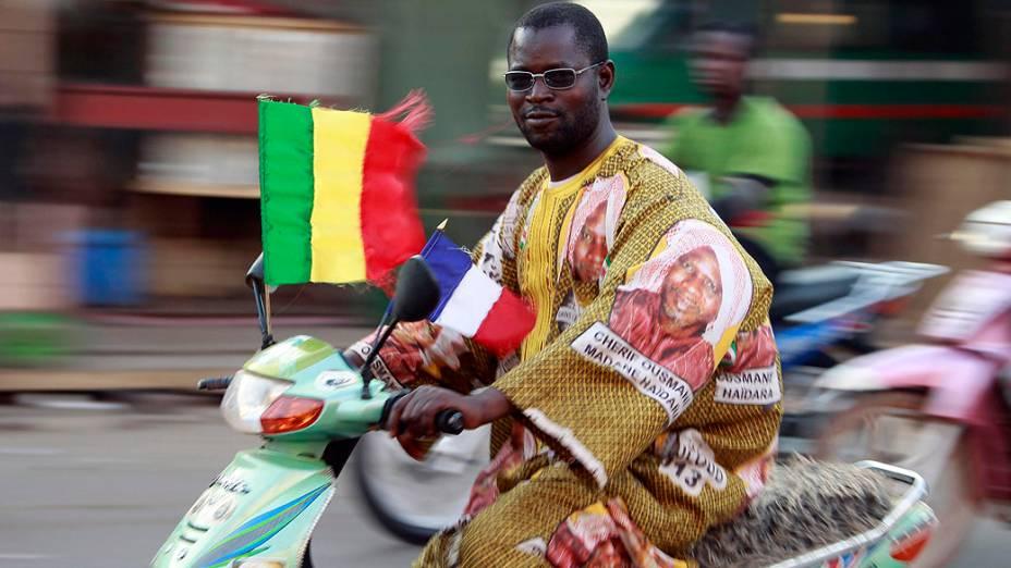 Em Bamako, motociclista anda com as bandeiras do Mali e da França