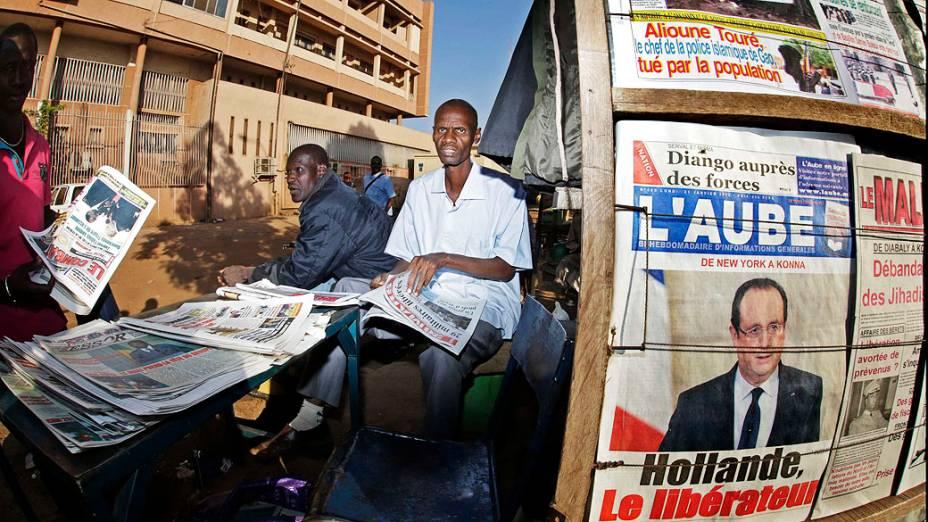Homem lê jornal ao lado de vendedor ambulante em Bamako. Na primeira página do jornal afixado à parede, abaixo da foto do presidente da França, a manchete Hollande, o Libertador