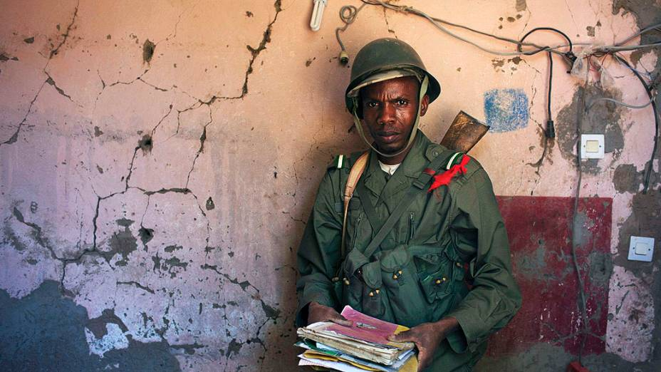 Soldado malinês segura documentos encontrados nos escombros de um acampamento militar em Diabaly