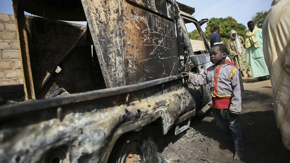 Criança observa veículo usado por terroristas e destruído por tropas francesas na cidade de Diabaly, Mali