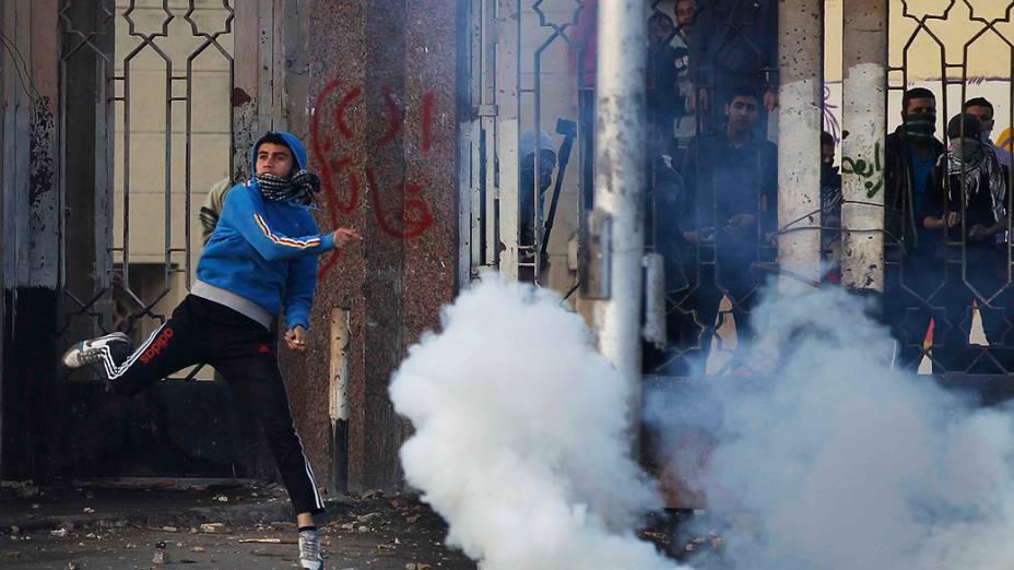 Um estudante da Universidade Al-Azhar, defensor da Irmandade Muçulmana e do presidente deposto Mohamed Mursi, joga uma pedra durante confrontos com a polícia e moradores no distrito de Nasr City, no Cairo - (27/12/2013)