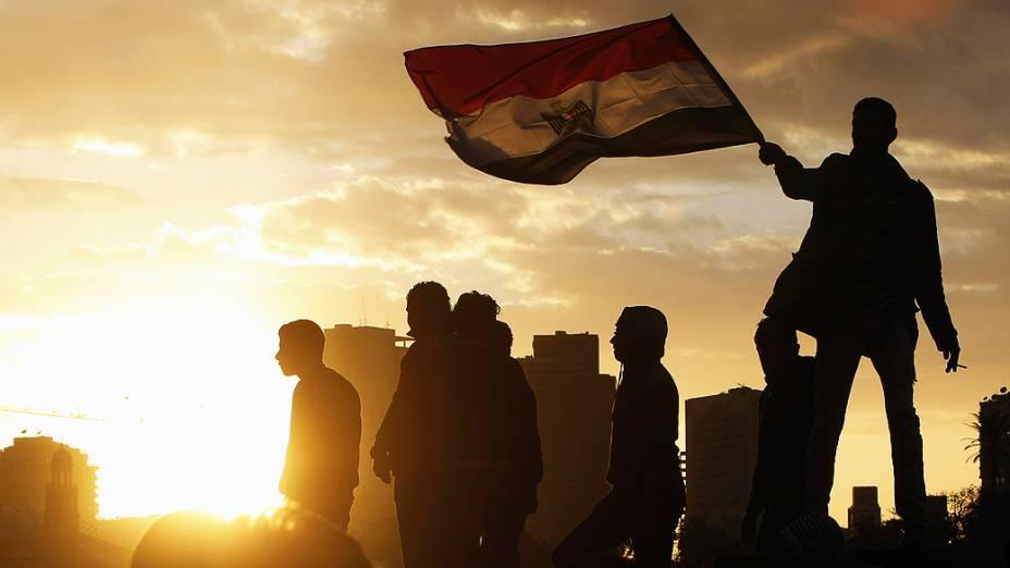 Manifestante conduz bandeira egípcia na ponte Kasr El Nile, Cairo