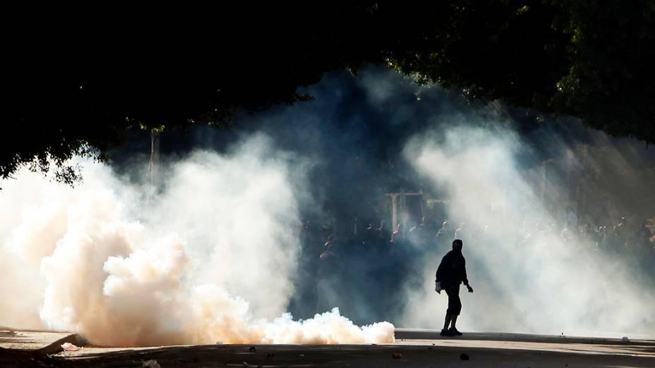 Manifestantes são vistos através da fumaça de bombas de gás lacrimogêneo usadas pela polícia durante os confrontos em Alexandria, nesta sexta feira (25)