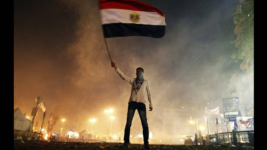 Manifestante conduz a bandeira egípcia em meio a fumaça de bombas de gás lacrimogênio durante protestos na praça Tahrir no Cairo, no segundo aniversário da revolta que derrubou o presidente Hosni Mubarak