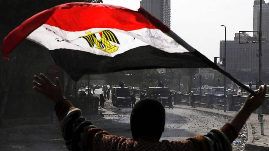 Manifestante conduz bandeira do Egito durante confrontos ao longo da ponte Qasr Al Nil, Cairo
