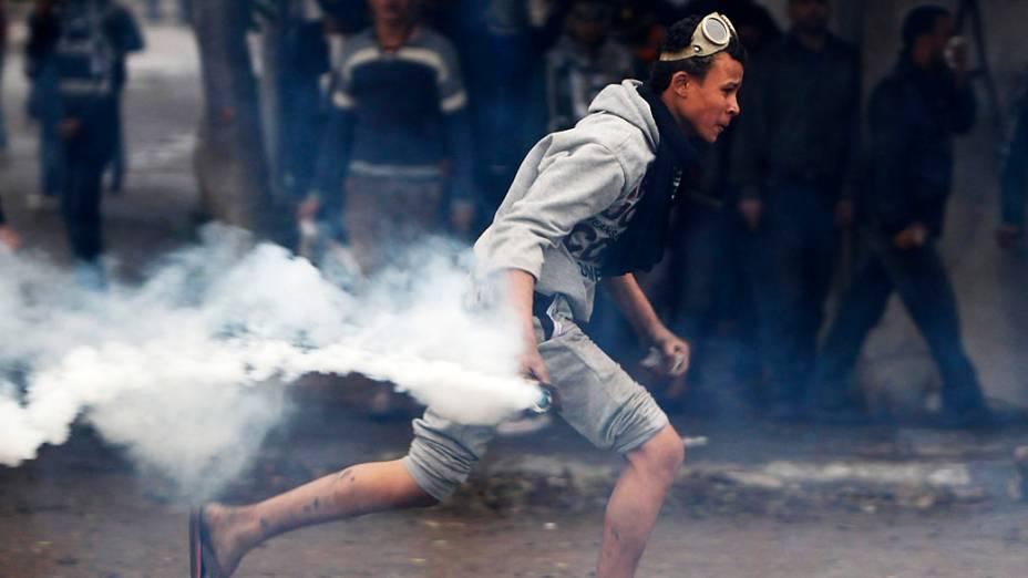 Manifestante se prepara para lançar bomba de gás lacrimogêneo de volta para a polícia durante confrontos na Praça Tahrir, Cairo