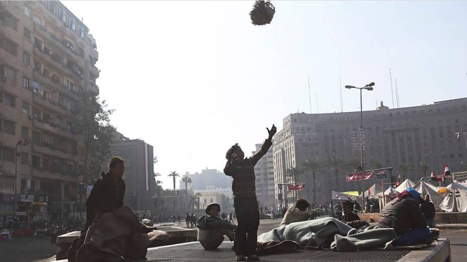 Crianças brincam em uma saída de ar da praça Tahrir, Cairo