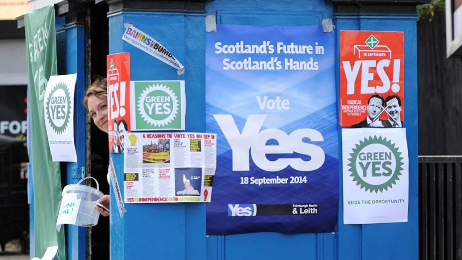 Partidária pela independência da Escócia pendura cartazes em sua banca, em Edimburgo