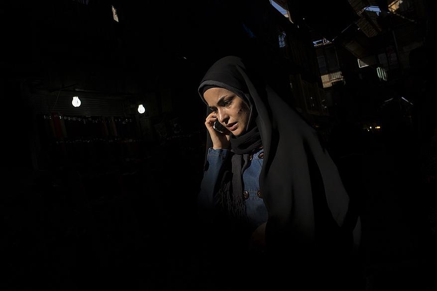 Mulher fala no celular no mercado de Teerã, no Irã