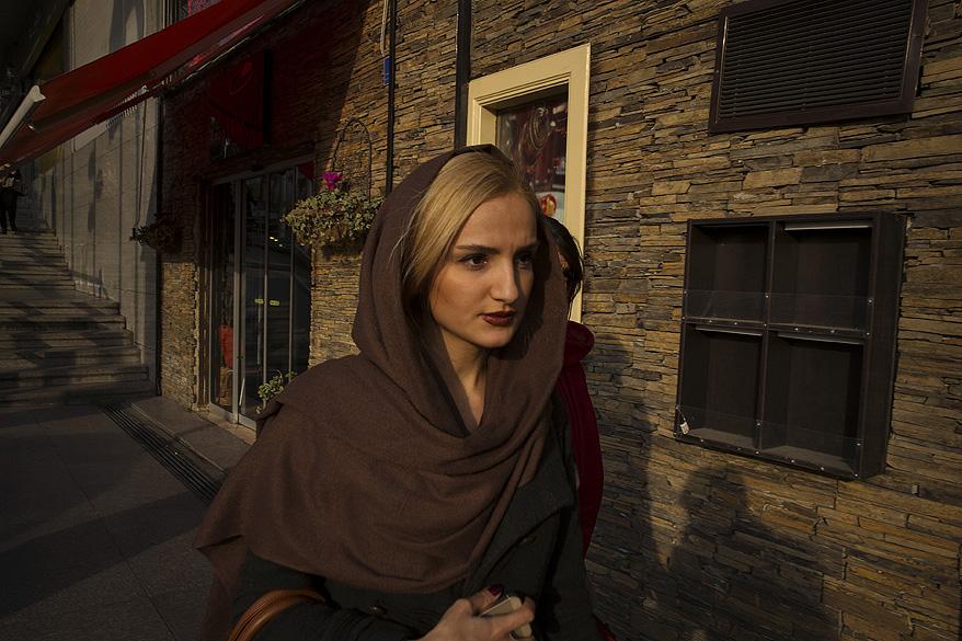 Mulher caminha em um bairro nobre da cidade de Teerã, onde as leis sobre as vestimentas estão mais liberais, no Irã