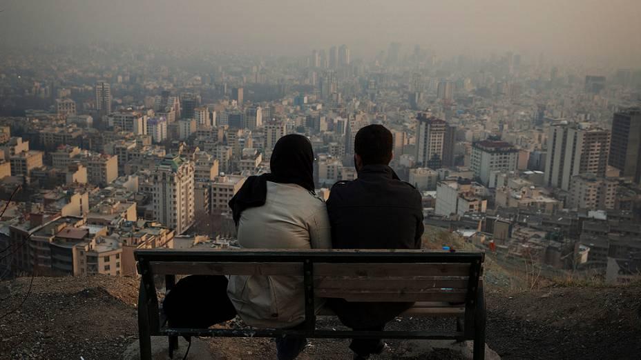 Um casal olha a cidade de Teerã do alto de uma colina, no Irã