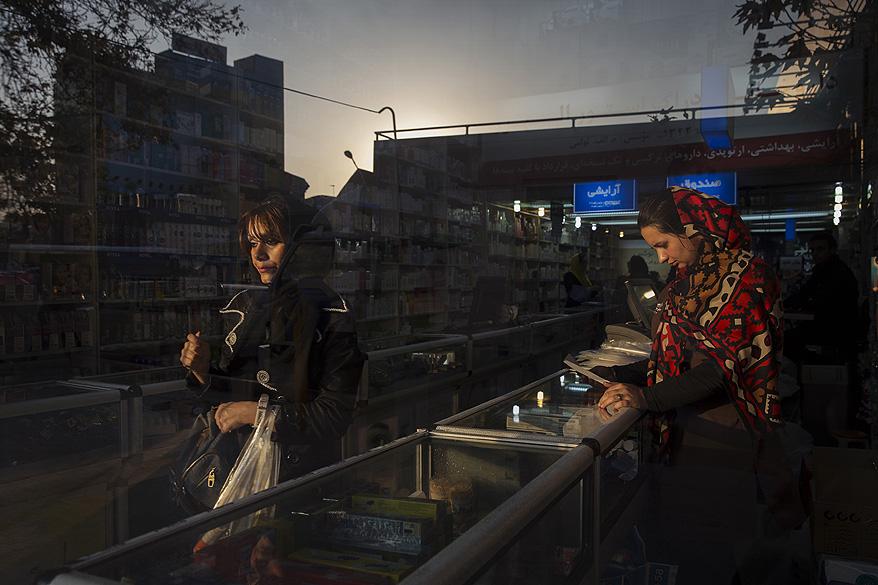 Rua de um bairro comercial é refletida na janela de uma farmácia na cidade de Teerã, no Irã