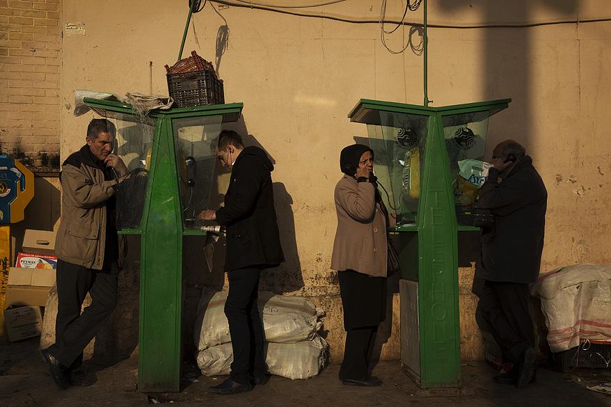 Pessoas falam em telefones públicos na cidade de Teerã, no Irã