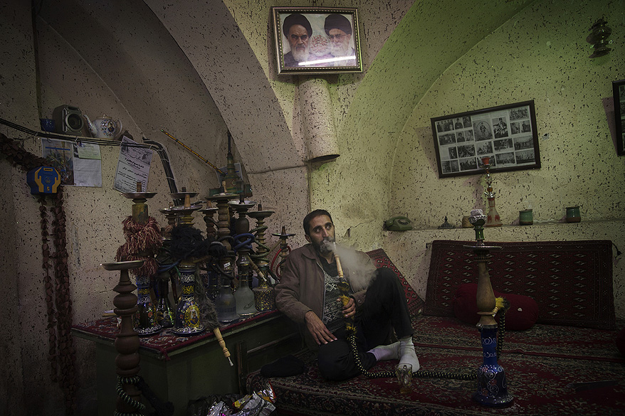 Homem fuma narguilé na cidade de Qom, no Irã