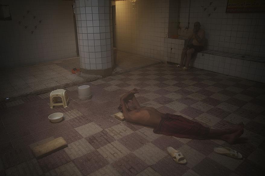 Homem descansa em uma casa de banho na cidade de Qom, no Irã