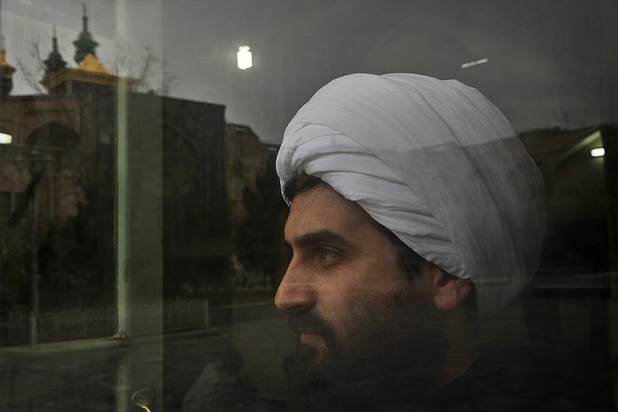 Homem olha por uma janela de uma sala de oração na universidade religiosa onde o Aiatolá Ruhollah Khomeini estudou, na cidade de Qom no Irã
