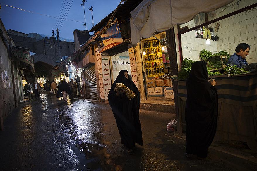 Mulheres vestidas com roupas conservadoras adam em um mercado, na cidade de Qom no Irã