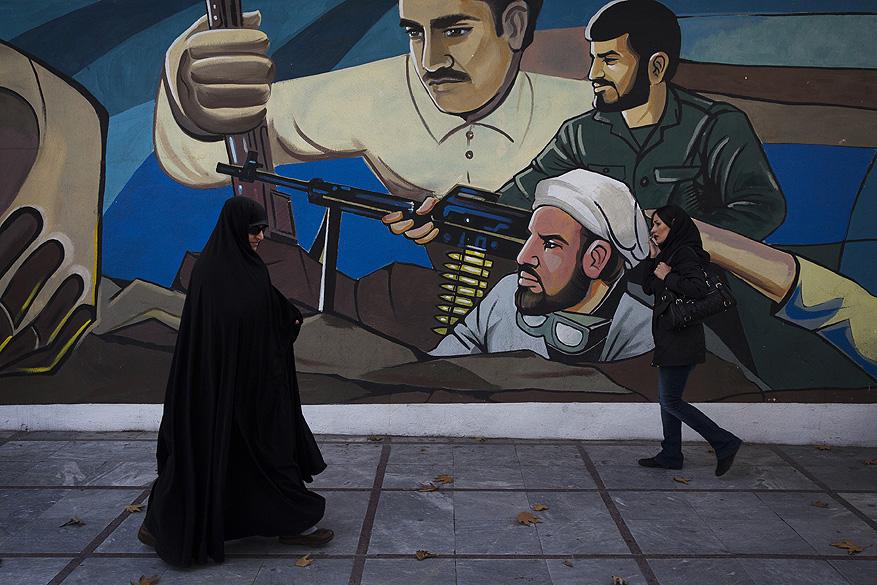 Pessoas caminham em frente a uma propaganda na cidade de Teerã, no Irã