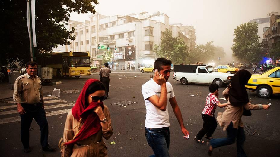 Pessoas andam pelas ruas de Teerã, capital do Irã, em meio a uma tempestade de areia