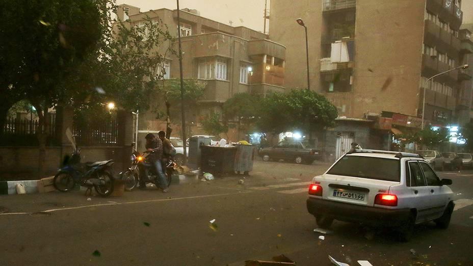 Motociclista se protege da tempestade de areia que atingiu Teerã, capital do Irã