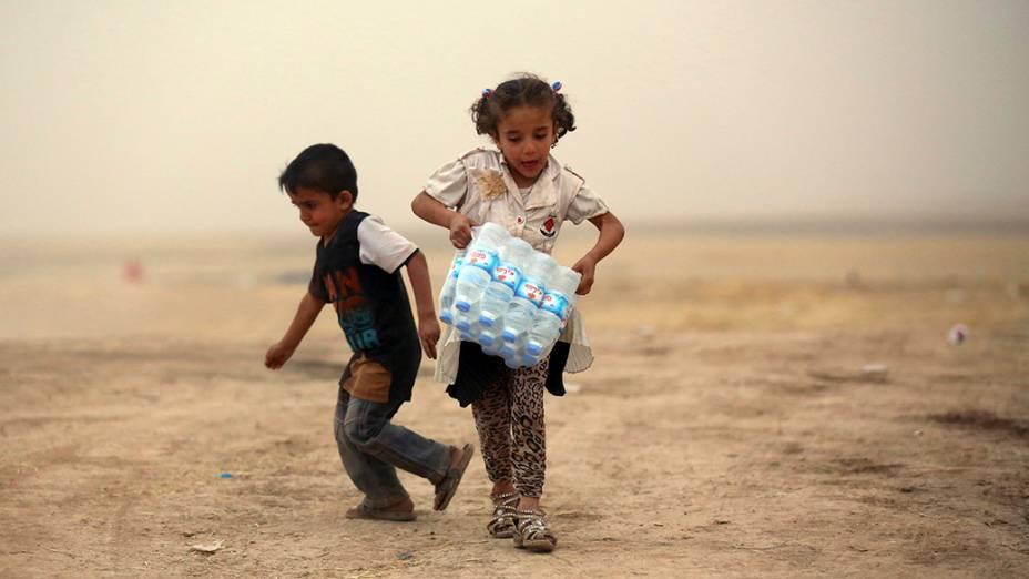 Crianças refugiadas da violência em Mosul, carregam água em um dos acampamentos nos arredores de Erbil, na região do Curdistão do Iraque
