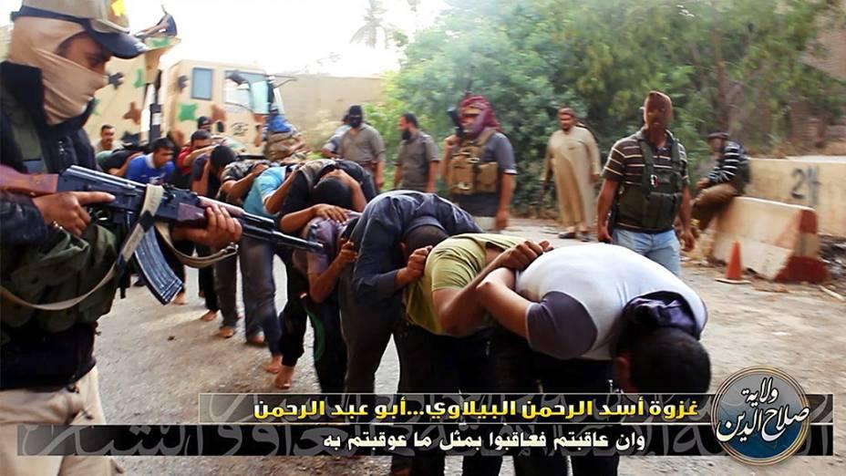 Imagem divulgada pelo site jihadista Welayat Salahuddin mostra militantes do Estado Islâmico do Iraque e do Levante (EIIL) ao lado de dezenas de iraquianos membros das forças de segurança antes de serem executados em um local desconhecido<br><br>