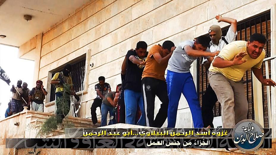 Imagem divulgada pelo site jihadista Welayat Salahuddin mostra militantes do Estado Islâmico do Iraque e do Levante (EIIL) ao lado de dezenas de iraquianos membros das forças de segurança antes de serem executados em um local desconhecido