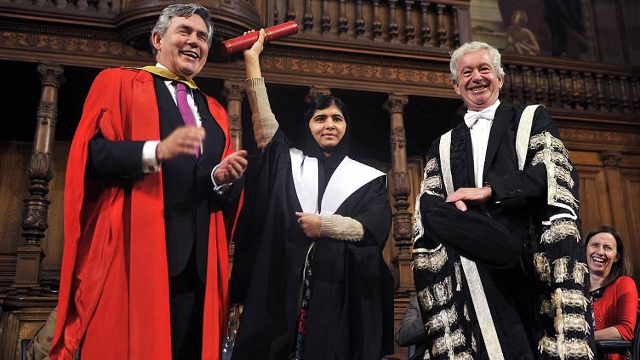 Malala Yousafzai recebe das mãos do ex-primeiro-ministro britânico Gordon Brown e do professor Timothy OShea, o título de mestrado honorário da Universidade de Edimburgo durante a primeira reunião da Comissão de Cidadania global da universidade, na Escócia