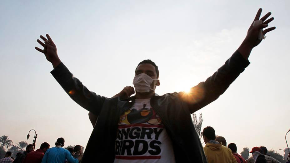Membro da Irmandade Muçulmana aponta o número quatro, na frente da polícia de choque ao longo de uma estrada em Kornish El Nile, que leva à Praça Tahrir, durante os confrontos com a polícia, no Egito (06/10/2013)
