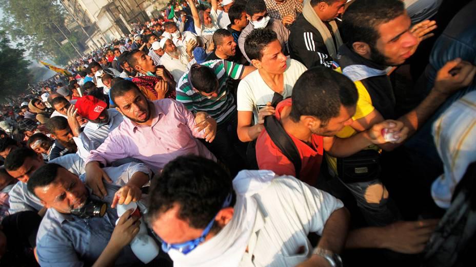 Membros da Irmandade Muçulmana e simpatizantes do deposto presidente egípcio, Mohamed Mursi recebem bomba de gás lacrimogêneo lançado pela polícia durante os confrontos ao longo de uma estrada em Kornish El Nile, que leva à praça Tahrir (06/10/2013)