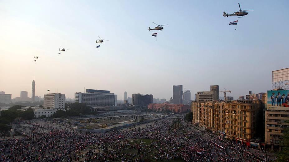 Helicópteros militares são vistos sobrevoando enquanto as pessoas se reúnem na Praça Tahrir para comemorar o aniversário de um ataque contra as forças israelenses durante a guerra de 1973, no Cairo (06/10/2013)