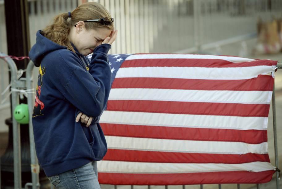 Jillian Blenis, cidadã de Boston, chora em frente a uma bandeira americana colocada na Boylston Avenue, em Massachusetts, Estados Unidos