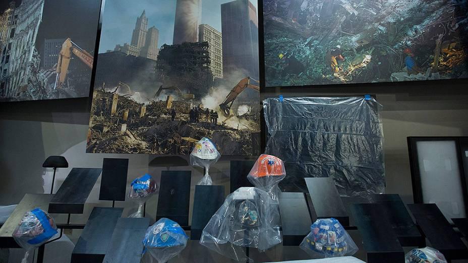 Capacetes usados por membros de equipes de emergência e órgãos públicos durante o resgate às vítimas estão expostos diante de fotografiasdo dia dos atentados em Nova York