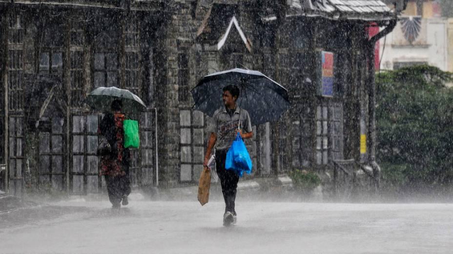 Pedestres caminham sob chuva forte na cidade de Shimla . As chuvas de monção registraram níveis médios mais elevados na primeira semana da estação chuvosa de quatro meses