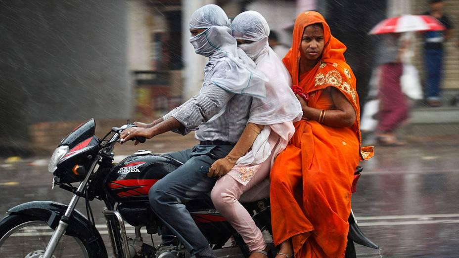 Homem monta uma motocicleta  junto com sua família durante uma chuva forte na cidade de Allahabad, norte da Índia