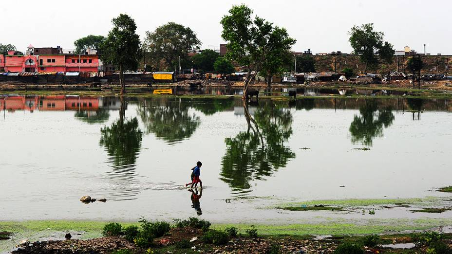 Crianças percorrem uma área submersa depois de uma chuva em Allahabad, na Índia