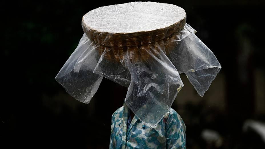 Um vendedor de peixe carrega sua cesta na cabeça coberta com plástico enquanto caminha durante a chuva em Mumbai, Índia