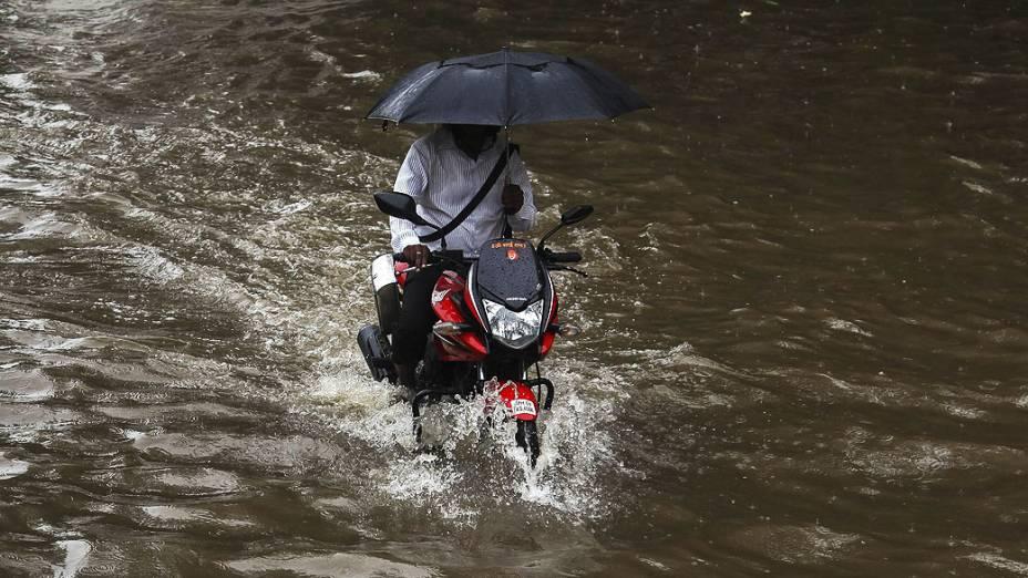 Homem passa por rua alagada com uma moto em Mumbai, na Índia