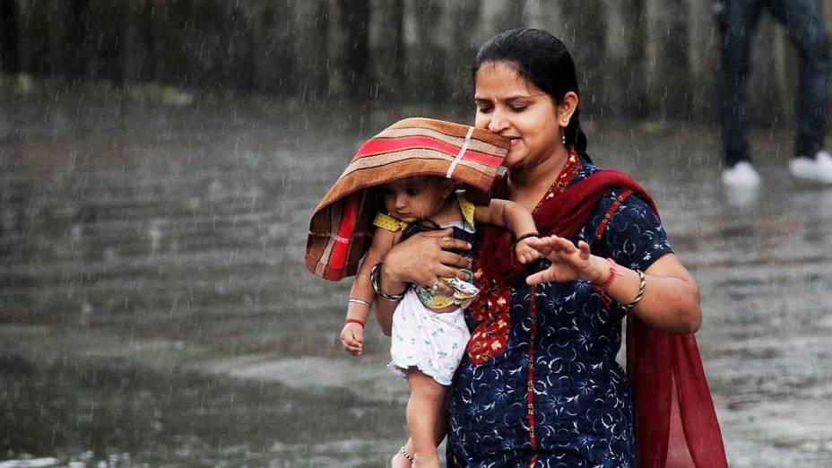 Mulher carrega seu filho durante chuva pesada na cidade de Chandigarh, na Índia