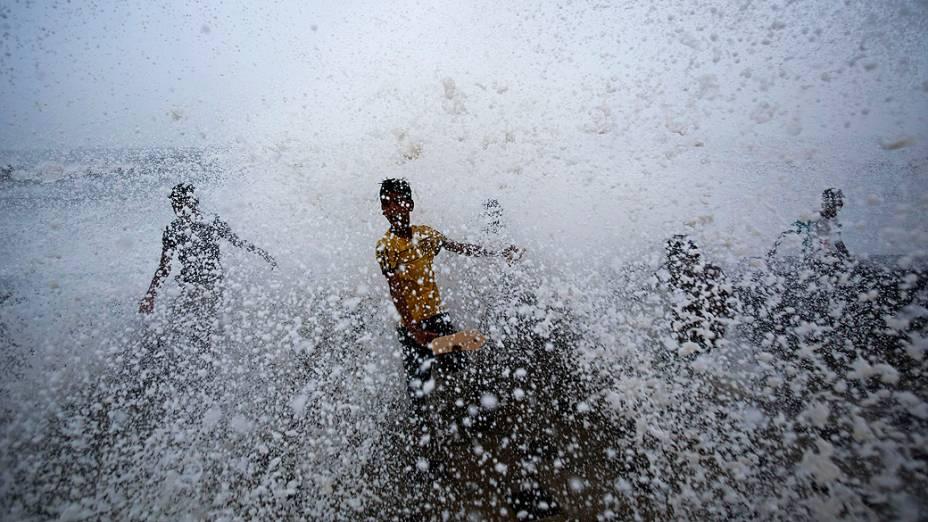 Meninos brincam em um paredão onde as ondas quebram durante uma chuva de monção em Mumbai, na Índia
