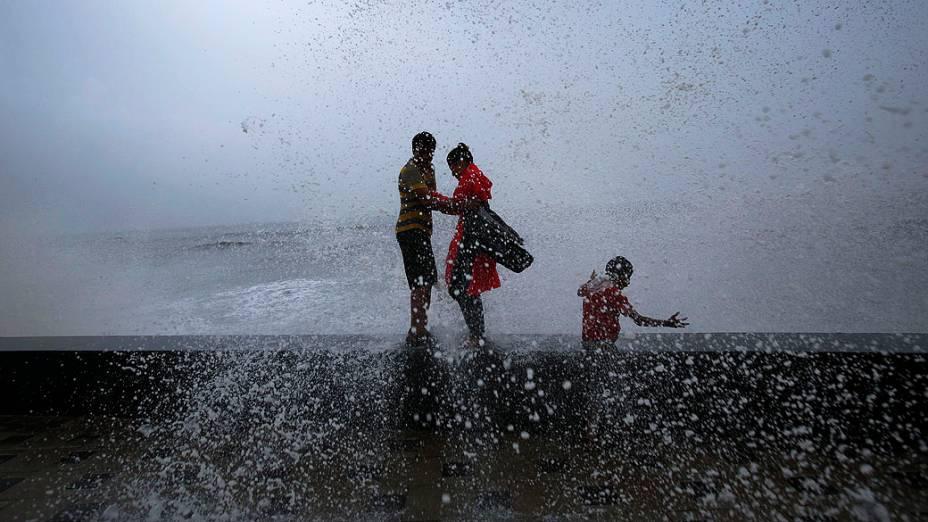 Casal se abraça enquanto ondas quebram sobre uma parede durante a temporada de monções da Índia, em Mumbai