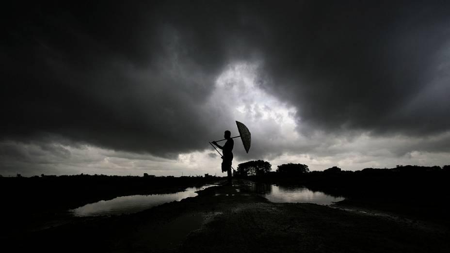 Um pastor de búfalos se protege da chuva e observa o rebanho,  enquanto as nuvens das monções pairam sobre um campo em Bhubaneswar, Índia